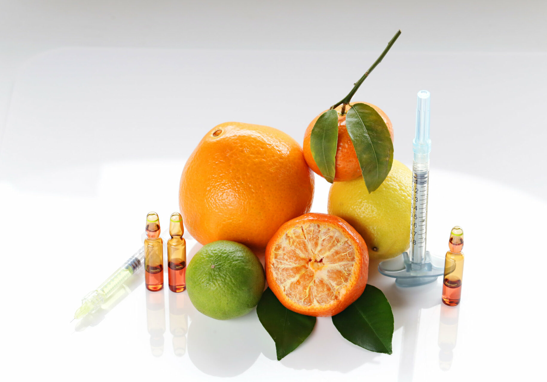Vitamin C in ampoules, two syringes, mandarin, lemon,  orange and lime on a light background.  Cosmetics Concept